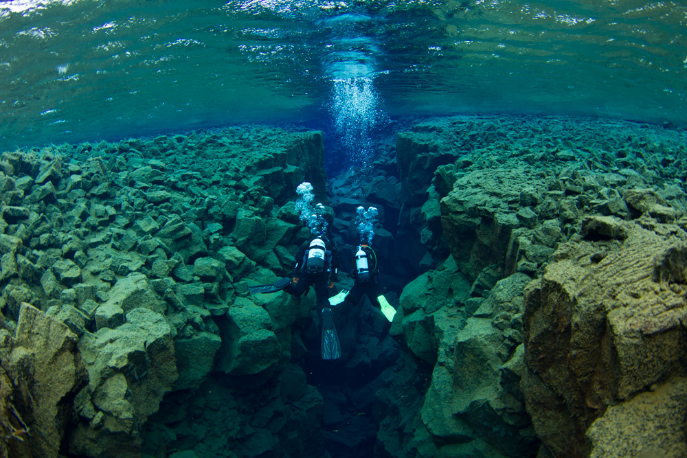 Divers glide through the Silfra tectonic fissure. Located between the North American and Eurasia tectonic plates in Iceland's Thingvallavatn National Park, this exotic dive site offers stunning geology and the clearest and most pristine water on the planet, with visibility limited only by the clarity of a diver's mask.